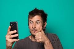 Гай делая selfie с смешными сторонами Гай фотографируя с его smartphone стоковое изображение