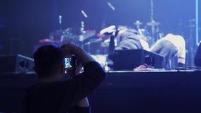 Гай держит камеру и принимает видео танцуя группы в составе молодые активные люди на этапе акции видеоматериалы