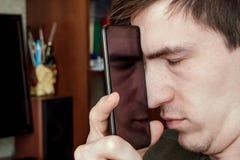 Гай закрыло его глаза и положило экран ` s smartphone к его стороне, отражение может быть увиденной половиной стороны внутри анфа Стоковое Изображение