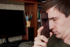 Гай закрыло его глаза и положило экран ` s smartphone к его стороне, отражение может быть увиденной половиной стороны внутри анфа Стоковая Фотография RF