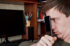 Гай закрыло его сторону, тайники за черным smartphone, на работая компьютере Стоковая Фотография