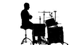 Гай играет музыку на барабанчике Белая предпосылка Силуэты Взгляд со стороны сток-видео