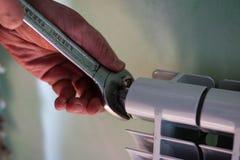 Гай использует ключ для того чтобы изменить вентиляционное отверстие сломанное радиатором Стоковое Фото