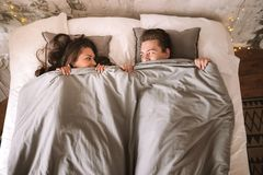 Гай и девушка лежат на кровати под серыми одеялами и взгляде на одине другого стоковые фотографии rf