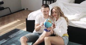 Гай и девушка сидя около кровати смотрят глобус выбирая место для того чтобы путешествовать на медовом месяце сток-видео
