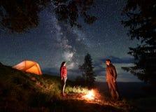 Гай и девушка стоят напротив одина другого и между ими огонь на ноче располагаясь лагерем в горах Стоковое фото RF