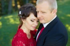 Гай и девушка нежно обняли один другого стоя в луге в парке Стоковое Изображение