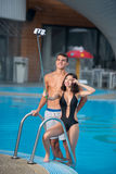 Гай и девушка представляя против бассейна с совершенной водой aqua и принимая фото selfie с monopod на курорте Стоковое Изображение RF