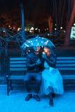 Гай и девушка сидя на стенде под зонтиком Стоковое Изображение RF