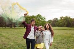 Гай и девушки идя с пирофакелом дыма Стоковая Фотография