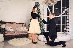 Гай на его колене и держит обручальное кольцо в его руке Предложите получить пожененный во времени рождества стоковые изображения rf