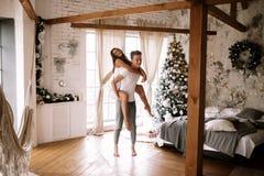 Гай одел в белой футболке и шорты держат девушку на его назад в уютной украшенной комнате с деревянными балками, новом стоковая фотография