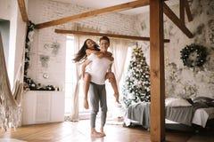 Гай одел в белой футболке и шорты держат девушку на его назад в уютной украшенной комнате с деревянными балками, новом стоковое фото rf