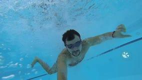 Гай принимая видео собственной личности пока бегущ, скачущ в бассейн и плавающ под водой видеоматериал