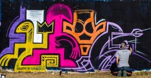 Гай рисует граффити на улице города стоковые изображения rf