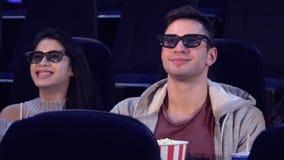 Гай сидит между 2 девушками на кинотеатре стоковые фото
