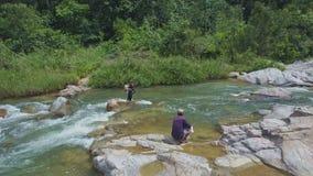 Гай сидит на камне среди речных порогов реки другое приносит сеть с рыбами сток-видео