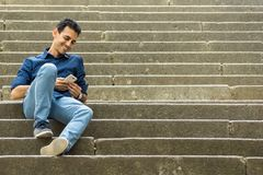 Гай сидя на лестницах со смартфоном стоковое фото