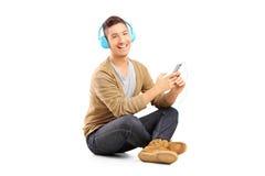 Гай сидя на поле и слушая музыке на наушниках Стоковое Изображение
