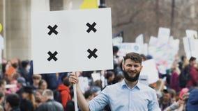Гай смотрит atcamera и улыбки на демонстрации Человек смеется над на ралли 4k