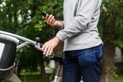 Гай стоя рядом с его телефоном велосипеда и обнесенное решеткой места в суде Стоковое Изображение RF