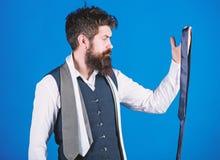 Гай с бородой выбирая галстук Проводник джентльмена Как выбрать правую связь : Как соответствовать галстуку  стоковое фото rf