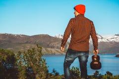 Гай с гитарой на предпосылке гор, лесов и озер, носит рубашку и красные шляпы Ослаблять и наслаждаться стоковые фото