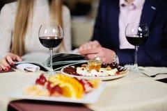 Гай с девушкой в ресторане выбирает блюда от меню Стоковые Фотографии RF