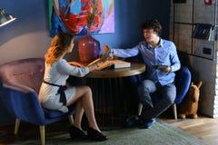 Гай с девушкой, друзьями, студентами сидя и говоря, телефон владением Стоковое Изображение
