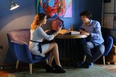Гай с девушкой, друзьями, студентами сидя и говоря, телефон владением Стоковая Фотография RF