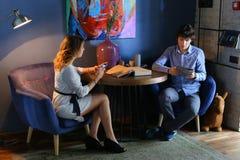 Гай с девушкой, друзьями, студентами сидя и говоря, телефон владением Стоковые Фото