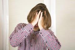 Гай с длинными волосами прячет сторону в руках Стоковая Фотография
