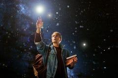 Гай с книгами достигает для звезд, концепции воображения стоковая фотография rf