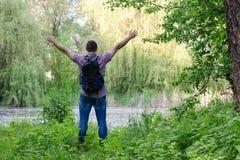 Гай с рюкзаком стоит на береге озера при протягиванные оружия, заднего взгляда леса Стоковые Изображения