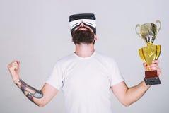 Гай с стеклами VR выиграло чемпионат, владение в кубке руки золотом Человек с бородой в стеклах VR победитель, серый стоковые фото