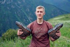 Гай с туристскими ботинками Стоковые Изображения