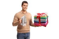Гай с утюгом и стогом упакованного и проутюживенного wrappe одежд Стоковые Фото