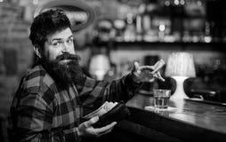 Гай тратит отдых в баре, defocused предпосылке Человек с жизнерадостной стороной гримасы сидит самостоятельно в баре или пабе око Стоковые Изображения