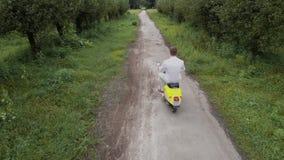 Гай управляет мопедом outdoors Снятый на трутне видеоматериал