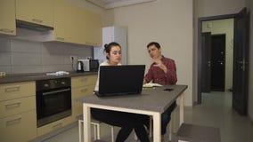 Гай учит, что девушка использует компьтер-книжку пока сидящ в кухне сток-видео