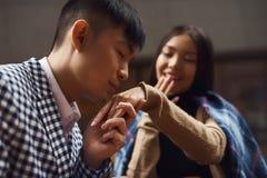 Гай целует руку девушки сидя на таблице в кафе Стоковые Изображения