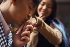 Гай целует руку девушки сидя на таблице в кафе Стоковое фото RF