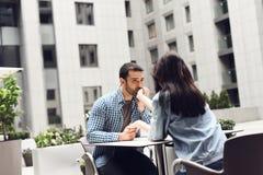 Гай целует руку девушки сидя на таблице в кафе Стоковая Фотография RF