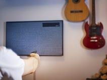 Гай, человек, каналы переключателя битника на ТВ, в дизайне комнаты с гитарой, отсутствие сигнала Стоковое Изображение