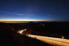 Галактика млечного пути со звездами и пылью космоса во вселенной и освещение на дороге перед утром на inthanon Чиангмае Doi, стоковые фотографии rf
