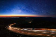 Галактика млечного пути со звездами и пылью космоса во вселенной и освещение на дороге перед утром на inthanon Чиангмае Doi, стоковая фотография
