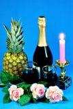 Гала-ужин, свет горящей свечи, вино, ананас, розы стоковое фото