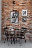Галерея черно-белых плакатов на кирпичной стене небольшой столовой внутренней с таблицей и черным стулом стоковая фотография rf