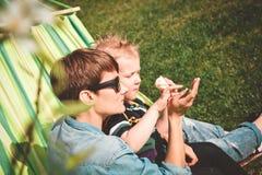 Гамак мамы и сына штрихуя зеленую ящерицу стоковое фото