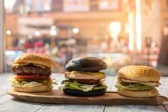 3 гамбургера на деревянной доске Стоковое Изображение RF